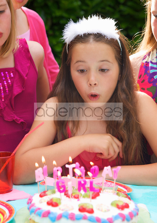 Close up of a young girl blowing out candles on a birthday cake