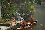 Monks collect alms in the early morning. In this town and village, they travel the canals by small boat.