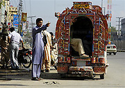 A suzuki cleaner waits for passengers at a bus stand in Islamabad, Pakistan on Wednesday Aug. 9, 2006.