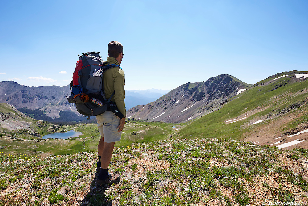 A backpacker stops to enjoy the view from a high elevation ridge in the Never Summer Wilderness, Colorado.