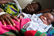 Mamie Sesay, 35, lies in bed with her newborn child as she recovers from surgery that saved her life at the Pujehun Government hospital in Pujehun, Sierra Leone on Friday March 19, 2010. After Mamie had given birth at a health center located 12 miles away, the nurse in charge struggled for two hours to extract the woman's placenta, that had remained blocked. She then called an ambulance that took six hours to get Mamie back to the hospital where she finally got treated. Medical staff said saving her was a miracle - she had been bleeding for 8 hours. This was Mamie's 10th pregnancy, four of which resulted in the death of the child. Her first child is 18 years old...