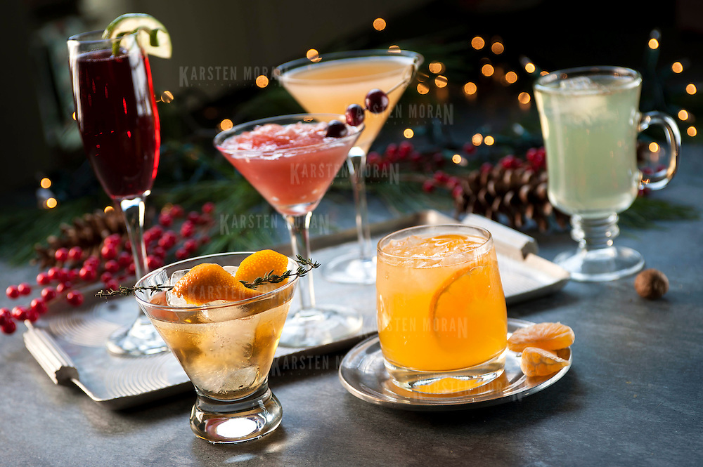 "December 2, 2013 - New York, NY : A selection of holiday cocktails, prepared and styled by Suzanne Lenzer, include, clockwise from foreground left, the ""Tabard Cocktail,"" (with sprig of Thyme) ""Christmas Spritz,"" (in champagne flute) ""Red Rooster,"" (with cranberries) ""Grapefruit-tini,"" (in far back) ""Green Tea Punch,"" and ""Bad Day at Work"" (garnished with clementines). CREDIT: Karsten Moran for The New York Times"