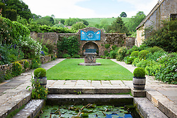 Well Court at Snowshill Manor with lily pond. The Nychthemeron clock on the wall