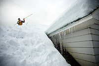 "JEROME A. POLLOS/Press..Mark McClain clears the snow from the roof of an elderly couple's home Wednesday  in Kellogg. ""I don't need a gym, I got aerobics on a roof,"" McClain said. The 45-year-old has been spending the last 10 days clearing roofs of businesses and homes."