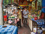 23 AUGUST 2014 - BANGKOK, THAILAND:          People walk between vendors selling food on the sidewalk along Chareon Krung Road in Bangkok. The Thai military junta, formally called the National Council for Peace and Order (NCPO), has ordered street vendors off of the sidewalks in an effort to bring order to Bangkok's chaotic sidewalks. Vendors have complained that the new regulations are hurting them economically but largely complied with the military orders.   PHOTO BY JACK KURTZ