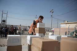 Licensed to London News Pictures. 20/10/2016. An aid worker picks up food and basic hygiene kits for Iraqi refugees that have recently arrived from areas liberated from the Islamic State in Iraq during the ongoing Mosul Offensive.<br /> <br /> The crowded Dibaga camp, housing around 28,000 Sunni Arab refugees, is the main gathering point for new IDPs now fleeing areas where ISIS have been pushed out or are in conflict with the Iraqi Army. Photo credit: Matt Cetti-Roberts/LNP