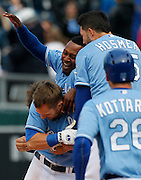 Kansas City Royals' Alex Gordon, bottom, is congratulated by his teammates including Jarrod Dyson, top left, and Eric Hosmer, top right, after his game-winning hit in the 10th inning of a baseball game against the Chicago White Sox at Kauffman Stadium in Kansas City, Mo., Sunday, May 5, 2013. the Royals beat the White Sox 6-5.  (AP Photo/Colin E. Braley).