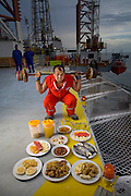 Oswaldo Gutierrez, Chief of the PDVSA Oil Platform GP 19 in Lake Maracaibo, Venezuela with his typical day's worth of food. (From the book What I Eat: Around the World in 80 Diets.) The caloric value of his day's worth of food on a day in December was 6000 kcals. He is 52 years of age; 5 feet, 7 inches tall; and 220 pounds. Gutierrez works on the platform for seven days then is off at home for seven days.   While on the platform he jogs on its helipad, practices karate, lifts weights, and jumps rope to keep fit. His food for the seven days comes from the platform cafeteria which, though plagued with cockroaches, turns out food choices that run from healthful to greasy-fried. Fresh squeezed orange juice is on the menu as well and Gutierrez drinks three liters of it a day himself. His diet changed about ten years ago when he decided that he'd rather be more fit than fat like many of his platform colleagues. PDVSA is the state oil company of Venezuela. MODEL RELEASED.