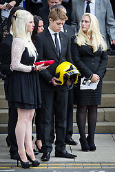 © Licensed to London News Pictures . 02/09/2013 . Bury , UK . Stephen Hunt's daughter Charlotte (left) and son Sam (centre) carry their father's medals and a fireman's helmet from the church after the service . The funeral of fireman Stephen Hunt at Bury Parish Church today (Tuesday 3rd September 2013) . Stephen Hunt died whilst tackling a blaze at Paul's Hair World in Manchester City Centre in July 2013 . Photo credit : Joel Goodman/LNP