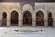 General view of central courtyard with prayer area in the background, Bou Inania Madrasa, Fez, Morocco, pictured on February 21, 2009 in the afternoon. The Bou Inania Madrasa was founded as a boarding school and mosque in AD 1351-56 by Abu Inan Faris, also the founder of the Bou Inania Madrasa in Meknes, and holds the status of Grand Mosque. A fine example of Marenid architecture with its intricate plasterwork, carved cedar and decorated tiles or zellij it is the only mosque in Fez open to non-Muslim visitors. It was renovated in the 18th and 20th centuries. Fez, Morocco's second largest city, and one of the four imperial cities, was founded in 789 by Idris I on the banks of the River Fez. The oldest university in the world is here and the city is still the Moroccan cultural and spiritual centre. Fez has three sectors: the oldest part, the walled city of Fes-el-Bali, houses Morocco's largest medina and is a UNESCO World Heritage Site;  Fes-el-Jedid was founded in 1244 as a new capital by the Merenid dynasty, and contains the Mellah, or Jewish quarter; Ville Nouvelle was built by the French who took over most of Morocco in 1912 and transferred the capital to Rabat. Picture by Manuel Cohen.