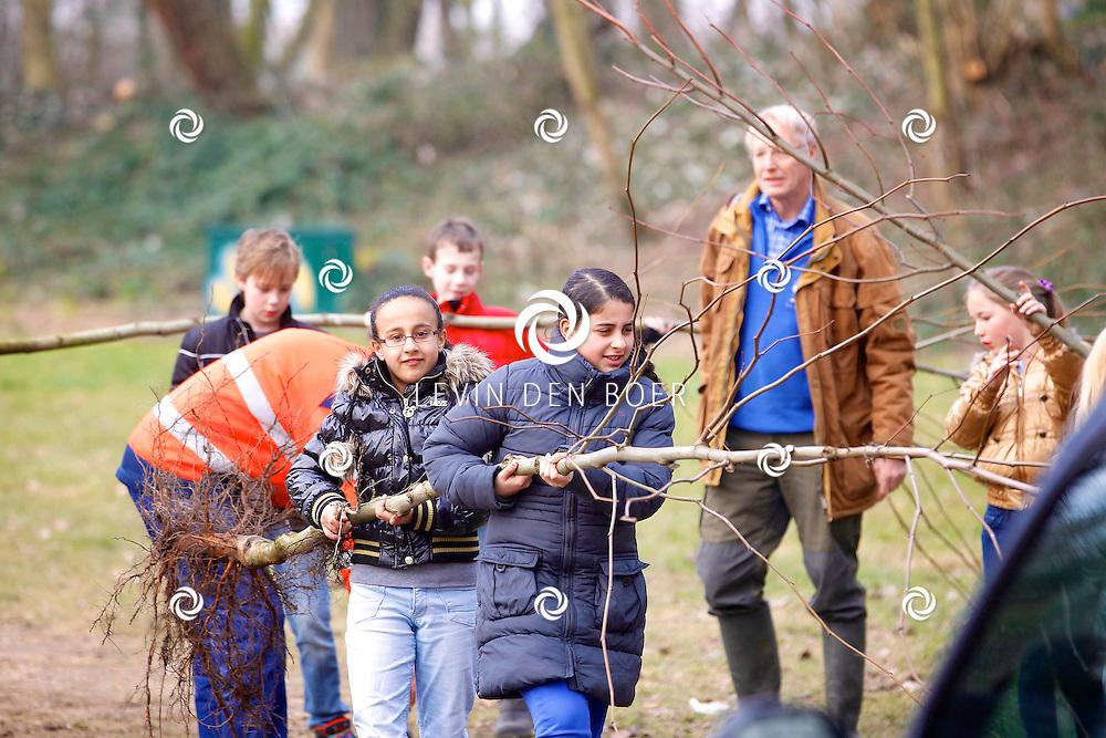 ZALTBOMMEL - In de kindertuin gingen scholieren druk aan de gang met het planten van nieuwe bomen op de nationale Boomplantdag 2013. FOTO LEVIN DEN BOER - PERSFOTO.NU