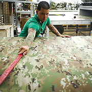 JUNE 28, 2016 --- COROZAL, PUERTO RICO<br /> Luis Vazquez, a cutting and fabric spreader at Bluewater Defense, flattens a roll of fabric laid out on the Gerber Machine (cutter). The company makes pants for the US Army.<br /> (Photo by Angel Valentin/Freelance)
