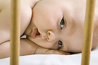 Infant child lying in cot