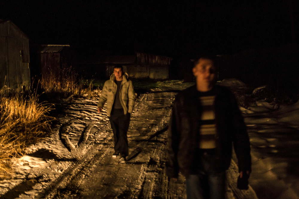 Maxim Makarov, left, and Vadim Kovalenko<br />  head out for the night on Saturday, October 26, 2013 in Baikalsk, Russia.