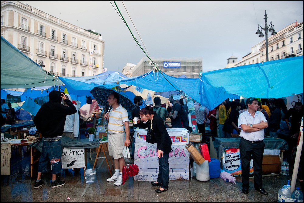 """Des fortes pluies tombent sur la camp sans pour autant decourager les campeurs. // Le mouvement spontane du """"15 M"""" (15 mai) compose de citoyens espagnols campe depuis 2 semaines sur la place Puerta Del Sol avec pour revendication la construction d'une democratie nouvelle. Organise en commission les citoyens prennent la parole lors d'assemblee ouverte a tous - Place Puerta Del Sol à Madrid le Juin 2011. ©Benjamin Girette/IP3Press"""