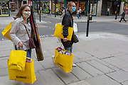 On the day that covid pandemic guidelines for shoppers in England mean that the wearing of face coverings in shops is mandatory, shoppers wearing face masks carry Selfridges shopping bags on Oxford Street, on 24th July 2020, in London, England.