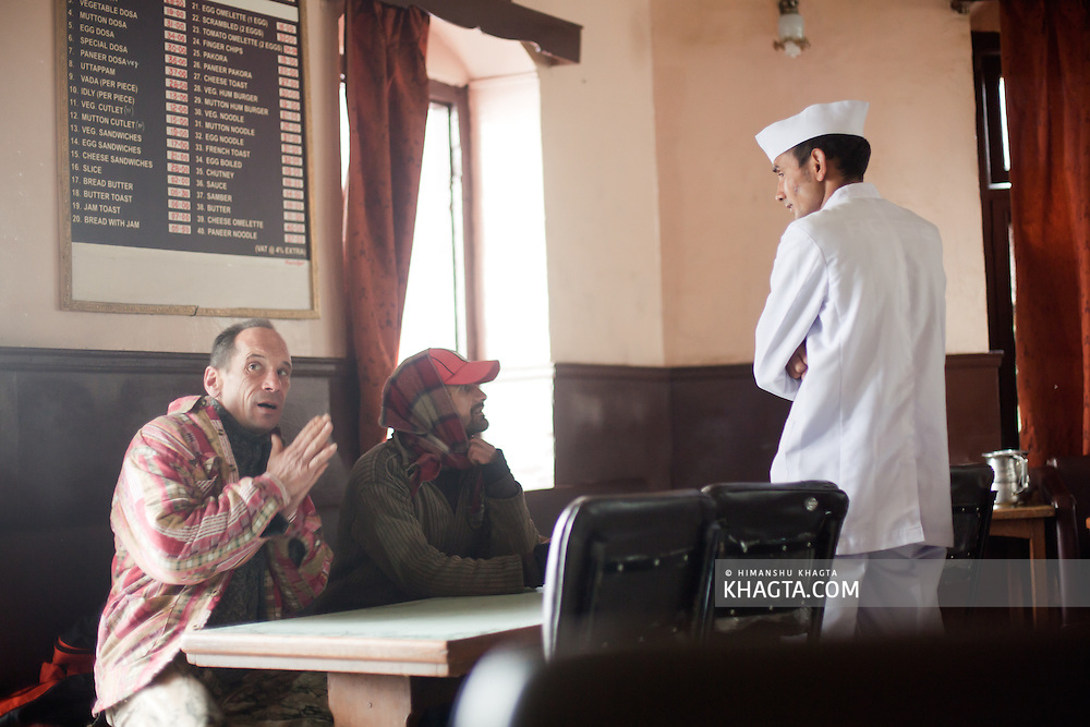 A waiter takes the order of the customers in a cold winter morning of Shimla.