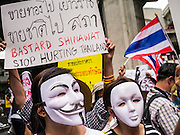 "02 JUNE 2013 - BANGKOK, THAILAND:   An anti-government protesters wearing Guy Fawkes masks march through the skywalk system in Bangkok. About 300 people wearing the Guy Fawkes mask popularized by the movie ""V for Vendetta"" and Anonymous, the hackers' group, marched through central Bangkok Sunday demanding the resignation of Prime Minister Yingluck Shinawatra. They claim that Yingluck is acting as a puppet for her brother, former Prime Minister Thaksin Shinawatra, who was deposed by a military coup in 2006 and now lives in exile in Dubai.   PHOTO BY JACK KURTZ"