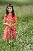 Girl (7-9) holding flowers in field portrait