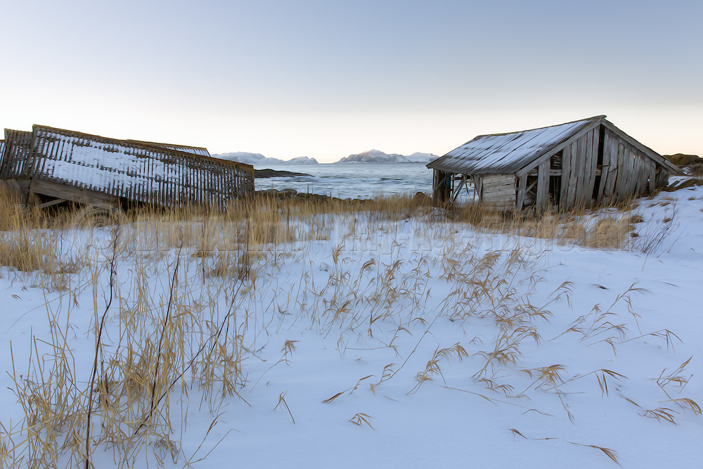 Old bouthouses by the sea in snow landscape. View to Nerlandsøy, Norway | Gamle naust ved sjøen i snølandskap. Utsikt mot Nerlandsøya.
