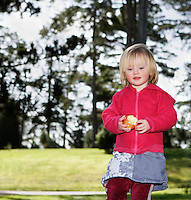 Girl (3-4) with apple outdoors