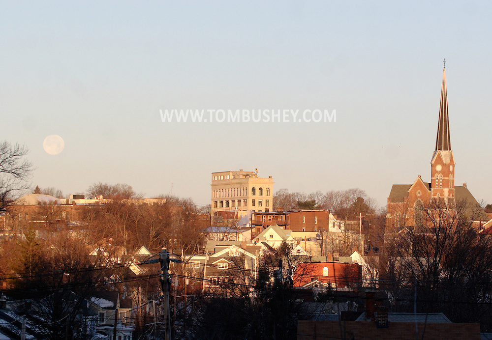 Middletown, NY - The full moon, at left, sets over buildings illuminated by the rising sun on the morning of Dec. 24, 2007.