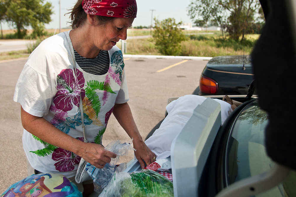 Lathan Goumas | The Bay City Times..Mary Ensman repacks a cooler with food after stopping to get ice at a gas station near the intersection of Interstate 75 and Linwood Road in Kawkawlin, MI. on Friday September 2, 2011. Ensman is driving north from Toledo, OH to camp with friends over the Labor Day weekend.
