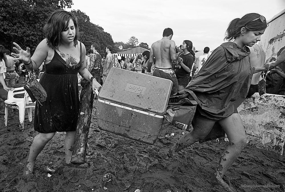 Friends struggle to carry a cooler through the the mud and mayhem.