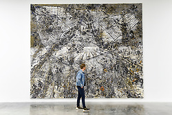 "© Licensed to London News Pictures. 14/11/2019. LONDON, UK. A visitor views ""Raum-Zeit"", 2019, by Anselm Kiefer at the preview of a new exhibition called ""Superstrings, Runes, The Norns, Gordian Knot"" by Anselm Kiefer.  The works include large scale paintings and installations that draw on the scientific concept of string theory and are on display at the White Cube Gallery in Bermondsey 15 November to 26 January 2020.  Photo credit: Stephen Chung/LNP"