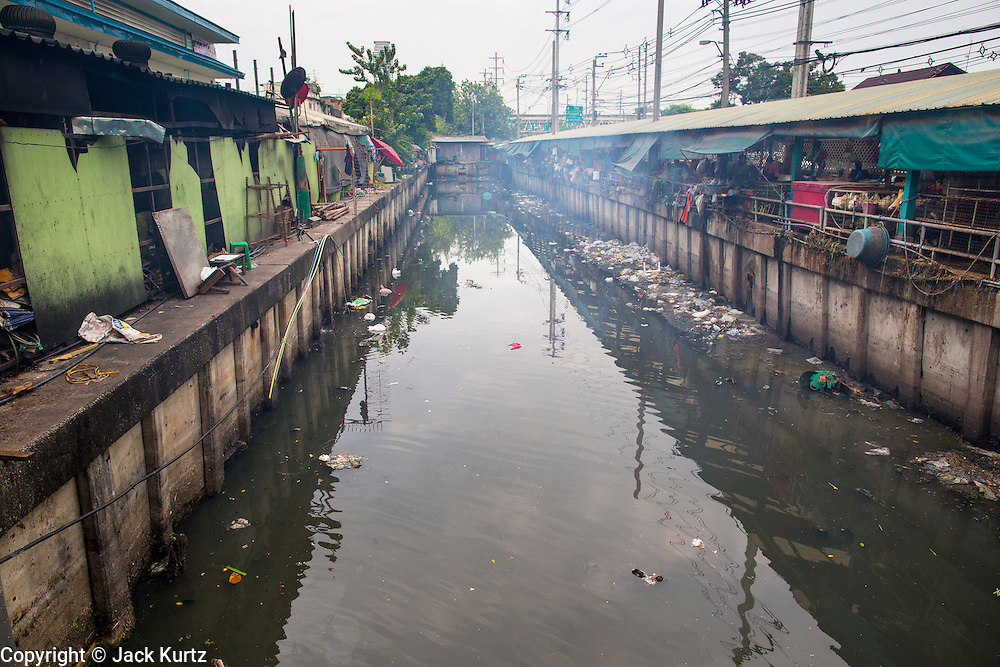 """03 OCTOBER 2012 - BANGKOK, THAILAND:  Khlong Toey runs along Khlong Toey Market in Bangkok. Khlong is the Thai word for canal. This canal used to go all the way to the old imperial center of Bangkok but has been filled in now. This stretch of the canal is used for waste water from the market. Khlong Toey (also called Khlong Toei) Market is one of the largest """"wet markets"""" in Thailand. Thousands of people shop in the sprawling market for fresh fruits and vegetables as well meat, fish and poultry every day.       PHOTO BY JACK KURTZ"""