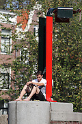 On an unseasonably warm day in Amsterdam in early October people sit out in the sun or mosey along the canals in their boats