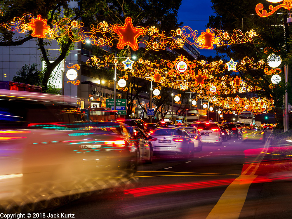 "12 DECEMBER 2018 - SINGAPORE:  Traffic on Orchard Road passes under Christmas lights decorated with Disney characters. Orchard Road is the main shopping district of Singapore and for years hosts a large light display around Christmas. The main sponsor of this year's display is the Disney Company and the displays are decorated with characters from the Disney entertainment universe. This has upset some religious leaders in Singapore and the National Council of Churches of Singapore (NCCS) sent a letter to the Singapore Tourism Board (STB) expressing its concern about the ""increasing secularisation and commercialization of Christmas"" in Singapore. The STB reached out to the NCCS, but the Orchard Road lights will remain on through the holidays.   PHOTO BY JACK KURTZ"