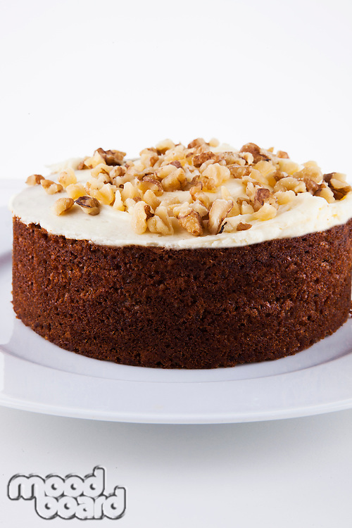 Close-up view of walnut cake in plate over white background