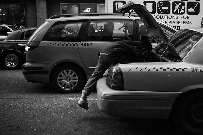 A man climbing into an New York taxi cab's car boot