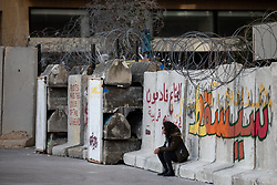 © Licensed to London News Pictures. 27/01/2020. Beirut, Lebanon. A woman sits on a security barricade around the government buildings in Downtown Beirut, as the government votes on the 2020 budget. Anti government demonstrators have been campaigning against government corruption and economic crisis for 103 days in Lebanon. Photo credit : Tom Nicholson/LNP