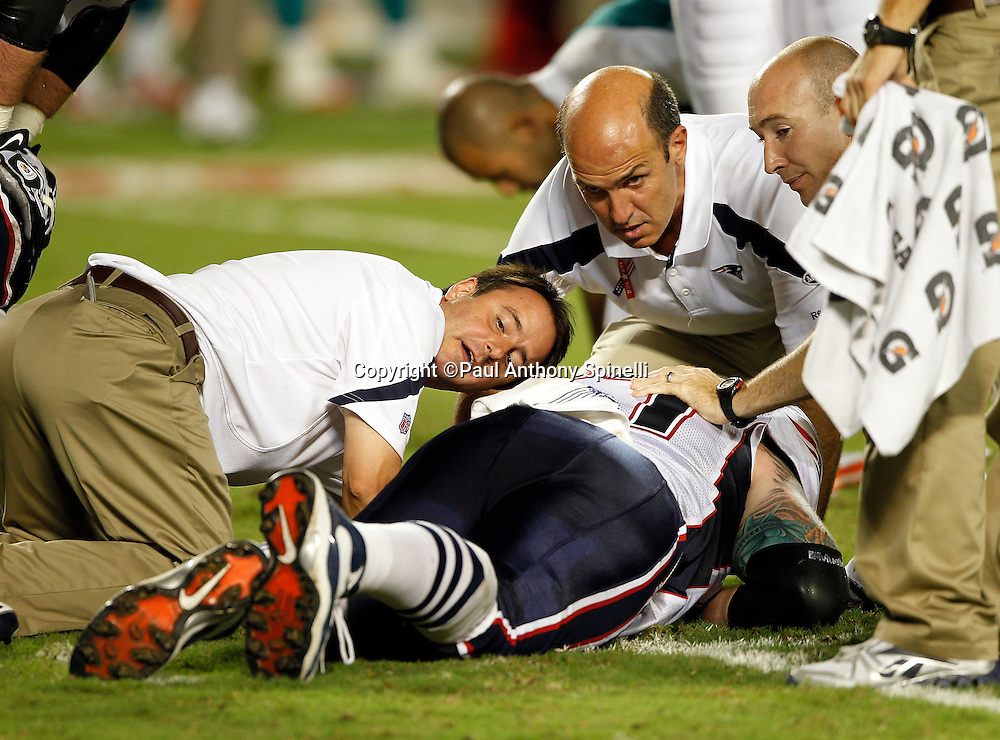 New England Patriots center Dan Koppen (67) gets medical attention after sustaining a leg injury during the NFL week 1 football game against the Miami Dolphins on Monday, September 12, 2011 in Miami Gardens, Florida. The Patriots won the game 38-24. ©Paul Anthony Spinelli