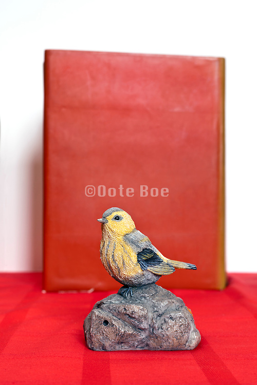 fake bird perched on a rock placed in front of a book