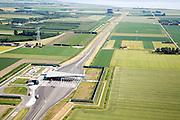 Nederland, Zeeland, Zuid-Beveland, 04-07-2006; luchtfoto : Borssele polder, tolplein Westerscheldetunnel, toegangsweg van de tunnel, richting Westerschelde (aan de horizon); aan weerszijden van deze toegangsweg zijn geluidswallen gebouwd om geluidsoverlast te voorkomen; deze geluidsschermen zijn in de vorm van dijken, passend in het omringende landschap (landschappelijke inpassing); privaat publieke samenwerking, PPS, tol, tolpoort, planologie, verkeer en vervoer, mobiliteit, auto, infrastructuur, milieu; zie ook andere (lucht)foto's van deze lokatie, deevan de serie Panorama Nederland.luchtfoto (toeslag); aerial photo (additional fee required); .foto Siebe Swart / photo Siebe Swart