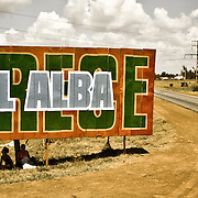 Cubans waiting to hitch a ride underneath a road sign promoting the growth of ALBA (Crece el ALBA). ALBA refers to the Bolivarian Alternative for the Americas; a Latin America Caribbean political alliance originally promoted by Simon Bolivar.