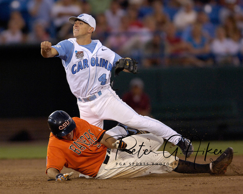 Oregon State's John Wallace (L) brakes up the double play, as North Carolina second basemen Garrett Gore (R) throws to first base in the seventh inning.  North Carolina defeated Oregon State 4-3 in the first game of the Championship Series at the College World Series at Rosenblatt Stadium in Omaha, Nebraska, June 24, 2006.