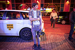 © Licensed to London News Pictures . 30/10/2016 . Manchester , UK . A man yawns as he stands waiting , holding a woman's handbag , outside a takeaway on Withy Grove . Revellers on a night out , many in fancy dress , on the weekend before Halloween . Photo credit : Joel Goodman/LNP