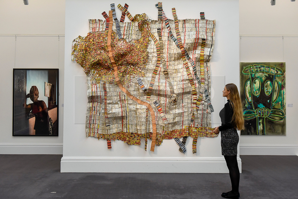 "© Licensed to London News Pictures. 12/05/2017. London, UK.   A staff member views (C) ""Earth Developing More Roots"", 2011, by El Anatsui (Ghana) (Est. GBP 650-850k) at the preview for the first sale dedicated to Modern and Contemporary African Art at Sotheby's New Bond Street.  The sale features over 115 artworks by over 60 different artists from 14 countries across the continent. Photo credit : Stephen Chung/LNP"