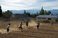 Kids playing soccer on a bare field in Bariloche, Argentina.