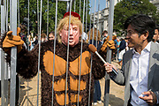 London, UK: The inflatable balloon called Baby Trump flies above a caged protestor Parliament Square in Westminster, the seat of the UK Parliament, during the US President's visit to the UK, on 13th July 2018, in London, England. Baby Trump is a 20ft high orange blimp depicting the US President as an enraged, smartphone-clutching infant - and given special permission to appear above the capital by London Mayor Sadiq Khan because of its protest rather than artistic nature. It is the brainchild of Graphic designer Matt Bonner. Photo by Richard Baker / Alamy Live News