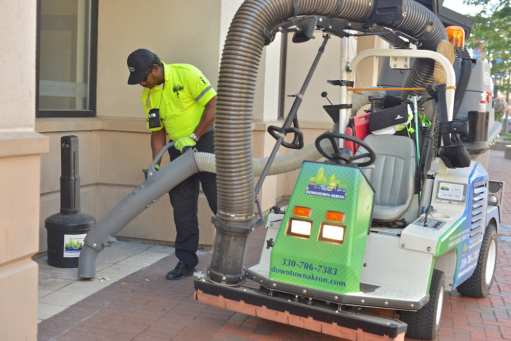 A Downtown Akron Partnership cleaning & safety ambassador cleaning the sidewalks of debris.