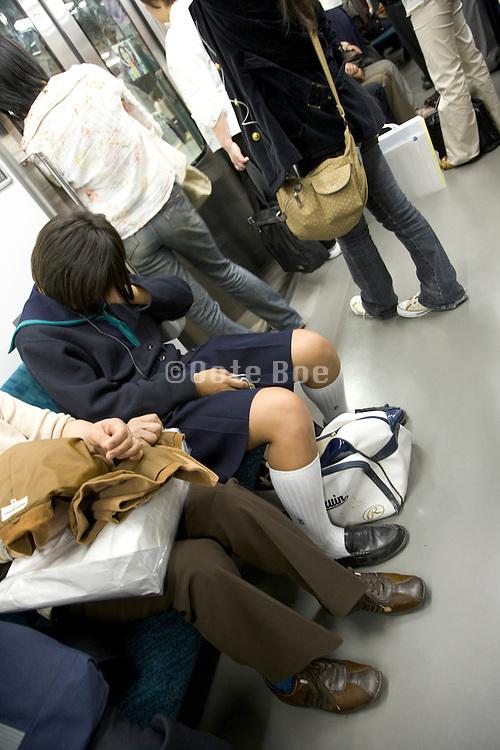 Japan school girl in uniform sleeping on the train