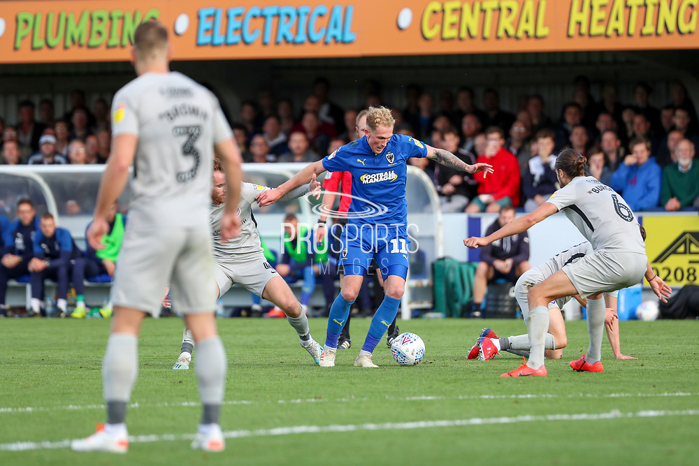 AFC Wimbledon midfielder Mitchell (Mitch) Pinnock (11) surrounded by players and dribbling during the EFL Sky Bet League 1 match between AFC Wimbledon and Portsmouth at the Cherry Red Records Stadium, Kingston, England on 19 October 2019.