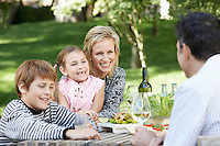 Family of four having picnic in park together portrait