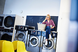 May 24, 2017 - Bored woman sitting on top of washing machine at laundrette (Credit Image: © Image Source via ZUMA Press)