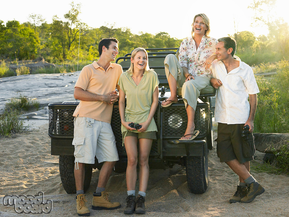 Group portrait of four people by jeep